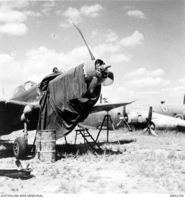 1945, un danneggiato P-40 Kittyhawk Curtiss del 450° Squadron RAAF sotto la manutenzione del meccanico. Non è in buone condizioni ma volerà di nuovo.