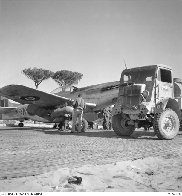 Marzo 1945, uno dei membri dell'equipaggio di terra fa rifornimento di carburante e armando con bombe un North American P51 Mustang.