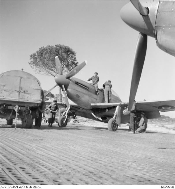 Marzo 1945, uno dei membri dell'equipaggio di terra fa rifornimento di carburante e arma con bombe un North American P51 Mustang prima di un'altra missione di perlustrazione a Bologna e nella Valle del Po, a sostegno dell'avanzata dell'Ottava Armata.